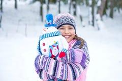 有雪人玩偶的愉快的冬天女孩 免版税库存图片