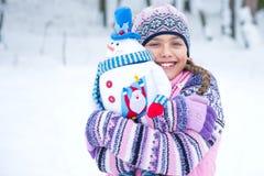 有雪人玩偶的愉快的冬天女孩 库存图片