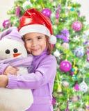 有雪人玩具的愉快的女孩 免版税图库摄影