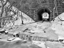有雪和冰被填装的小河的隧道 免版税图库摄影