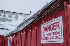有雪和危险标志的老屋顶 免版税库存图片