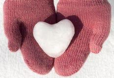 有雪心脏的桃红色手套 免版税库存照片