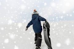 有雪撬上升的雪小山的小男孩在冬天 库存照片
