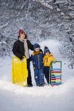 有雪撬的三个愉快的男孩 库存图片