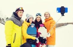 有雪板和智能手机的愉快的朋友 免版税图库摄影