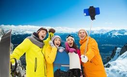 有雪板和智能手机的愉快的朋友 库存照片