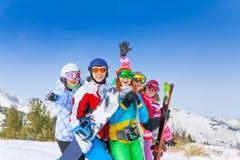 有雪板和滑雪的五个愉快的朋友 免版税库存照片