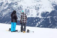 有雪板的二个人为倾斜做准备 免版税库存图片