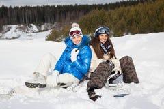 有雪板的二个女孩坐雪 免版税库存照片
