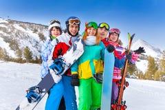 有雪板的五个愉快的微笑的朋友 库存照片