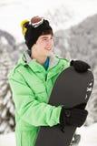 有雪板的十几岁的男孩在滑雪节假日 免版税图库摄影