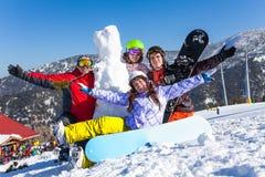 有雪板的四个愉快的朋友和雪人 免版税库存照片