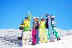 有雪板的四个愉快的朋友 免版税图库摄影