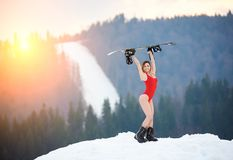 有雪板的女子挡雪板在冬天滑雪胜地的多雪的倾斜 库存照片