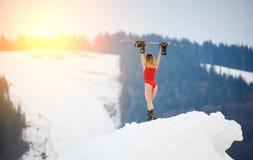 有雪板的女子挡雪板在冬天滑雪胜地的多雪的倾斜 库存图片