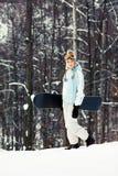 有雪板的少妇在滑雪倾斜 库存图片