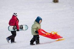 有雪板的有把手的孩子和爬犁 图库摄影