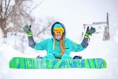 有雪板的美丽的愉快的年轻挡雪板女孩 免版税库存照片