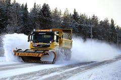 有雪犁的富豪集团FM卡车清除冬天路 免版税库存图片