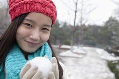 有雪球的少妇,微笑和看照相机 图库摄影