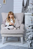 有雪球的愉快的矮小的微笑的女孩在圣诞树附近 免版税库存图片