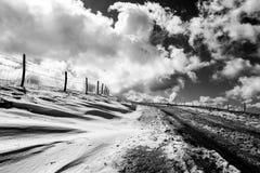 有雪的一条山路在边,在与whi的深天空下 库存图片