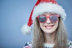 有雪的冻女孩在戴圣诞老人帽子和太阳镜的面孔 库存图片