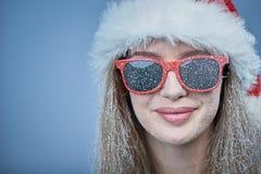 有雪的冻女孩在戴圣诞老人帽子和太阳镜的面孔 免版税库存照片