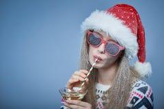 有雪的冻女孩在戴圣诞老人帽子和太阳镜的面孔 免版税图库摄影