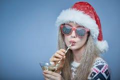 有雪的冻女孩在戴圣诞老人帽子和太阳镜的面孔 免版税库存图片