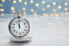 有雪的怀表在反对被弄脏的光的桌上 christmas countdown 库存照片