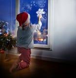 有雪花的小男孩装饰窗口的 库存照片