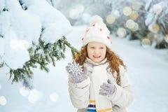 有雪花的笑的女孩在他的手上,在冬天公园 免版税库存图片