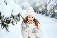 有雪花的笑的女孩在他的手上,在冬天公园 免版税图库摄影