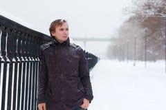 有雪花的年轻人在头发站立近的篱芭 图库摄影
