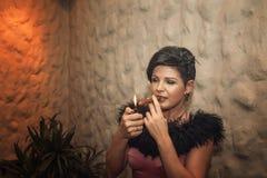 有雪茄的可爱的妇女 图库摄影