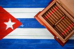 有雪茄的雪茄盒在古巴旗子背景 免版税库存图片