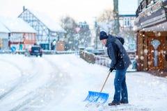 有雪铁锹的人在冬天清洗边路 免版税库存图片