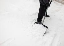 有雪铁锹的人清洗边路 库存照片