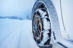 有雪链子的汽车在积雪覆盖的路的轮胎的 免版税库存照片