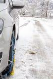 有雪链子的汽车在被冰的街道上 库存照片