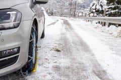 有雪链子的汽车在被冰的街道上 库存图片