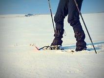 有雪靴步行的人腿在雪 冬天高涨细节在随风飘飞的雪的 免版税库存照片