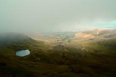 有雾的云彩和一个暗藏的秘密在笔y爱好者峰顶,布雷肯比肯斯山,威尔士,英国附近迷惑了小山的(Llyn Cwm Llwch)湖 免版税库存图片