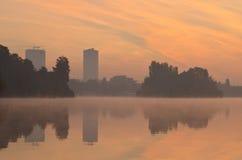 有雾的城市湖在黎明 免版税库存照片