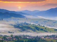 有雾的夏天早晨在山村 免版税库存照片
