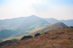 有雾的山路去在它上面在日落风景的小山 免版税库存图片