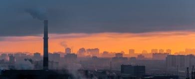 有雾的工业城市烟雾和日落的全景 免版税库存照片