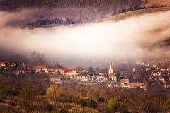 有雾的村庄在特兰西瓦尼亚 库存图片