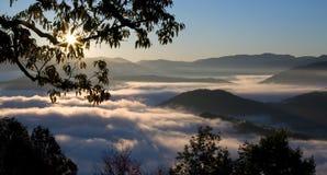 有雾的极大的山发烟性日出 免版税库存图片